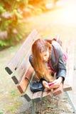 Adolescente, cara abajo en SMS de una escritura del banco Imagen de archivo libre de regalías