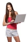 Adolescente castana con il computer portatile su fondo bianco Fotografia Stock