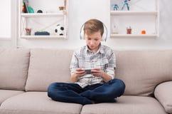 Adolescente casual que juega al juego móvil en casa Fotos de archivo