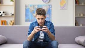 Adolescente caucásico adicto del artilugio que juega al juego en el smartphone, perdiendo tiempo metrajes