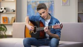 Adolescente caucásico alegre que toca la guitarra, disfrutando de la afición preferida, ocio almacen de metraje de vídeo