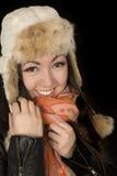Adolescente caucásico asiático acurrucandose su bufanda y sombrero del invierno Imagenes de archivo