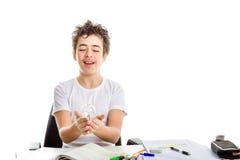Adolescente caucásico del acné que sostiene la bombilla de cristal real en homewor Fotografía de archivo