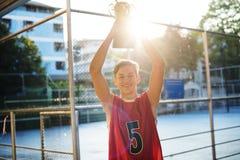 Adolescente caucásico en ropa deportiva que soporta un trofeo al aire libre Imagen de archivo libre de regalías