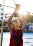 Adolescente caucásico en ropa deportiva que soporta un trofeo al aire libre Imagenes de archivo