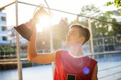 Adolescente caucásico en ropa deportiva que soporta un trofeo al aire libre Imagen de archivo