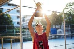 Adolescente caucásico en ropa deportiva que soporta un trofeo al aire libre Fotos de archivo libres de regalías