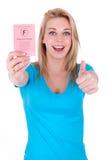 Adolescente caucásico feliz que muestra su carné de conducir  Fotografía de archivo libre de regalías