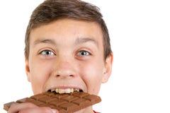 Adolescente caucásico joven con una barra del chocolate Fotografía de archivo