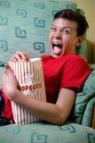 Adolescente caucásico joven que mira una película asustadiza Foto de archivo