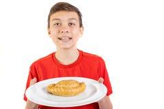 Adolescente caucásico joven que sostiene una placa y un pastel Imagen de archivo