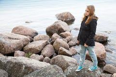 Adolescente caucásico que camina en piedras costeras Foto de archivo libre de regalías