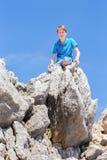 Adolescente caucásico que se sienta encima de rocas Imagenes de archivo