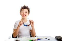 Adolescente caucasiano da acne que guarda monóculos do cinema 3D ao fazer Imagem de Stock