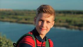Adolescente caucasiano do menino do retrato ascendente próximo em uma camisa vermelha com uma trouxa em sua parte traseira, no po video estoque