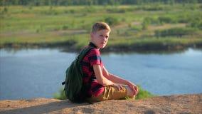 Adolescente caucasiano do menino do retrato ascendente próximo em uma camisa vermelha com uma trouxa em sua parte traseira, no po vídeos de arquivo