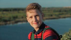 Adolescente caucasiano novo do menino do retrato em uma camisa vermelha com uma trouxa no seu para trás, no por do sol, sentando- video estoque