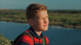 Adolescente caucasiano novo do menino do retrato em uma camisa vermelha com uma trouxa em sua parte traseira, no por do sol, sent video estoque