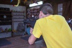 Adolescente caucasiano que aponta com o rifle pneumático preto em um galery de tiro, vista traseira foto de stock