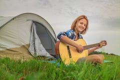 Adolescente cerca de la tienda que toca una guitarra Foto de archivo