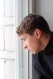 Adolescente cerca de la ventana Imagen de archivo
