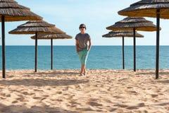 Adolescente cerca de los paraguas en la playa Imagenes de archivo