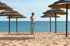 Adolescente cerca de los paraguas en la playa Imagen de archivo libre de regalías