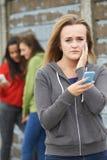 Adolescente che è oppresso dal messaggio di testo fotografia stock