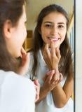 Adolescente che applica rossetto Fotografia Stock