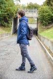 Adolescente che cammina da solo in via con lo zaino Fotografia Stock Libera da Diritti