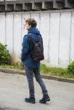 Adolescente che cammina da solo in via con lo zaino Immagine Stock