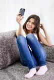 Adolescente che cattura le maschere con il telefono mobile Fotografia Stock