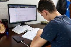 Adolescente che fa compito con il computer Immagini Stock Libere da Diritti