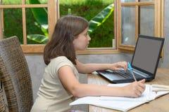 Adolescente che fa il suo compito con il computer portatile Fotografia Stock