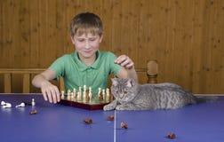 Adolescente che gioca scacchi con un gatto su una tavola di tennis Fotografia Stock