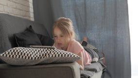 Adolescente che gioca sul pc della compressa che riposa su un sof? a casa Concetto della gente, di tecnologia e di svago video d archivio