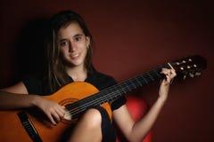 Adolescente che gioca una chitarra acustica Fotografia Stock Libera da Diritti