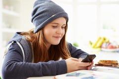 Adolescente che invia messaggio di testo mentre studiando Immagine Stock