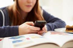 Adolescente che invia messaggio di testo mentre studiando Immagini Stock Libere da Diritti