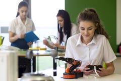 Adolescente che lavora al braccio robot Fotografie Stock Libere da Diritti