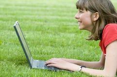 Adolescente che lavora al calcolatore sull'erba Fotografia Stock