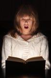 Adolescente che legge libro emozionante Fotografie Stock