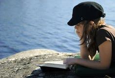 Adolescente che legge un libro esterno Fotografia Stock