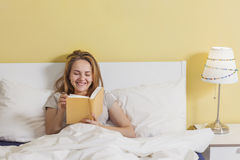 Adolescente che legge un libro a letto Fotografie Stock Libere da Diritti