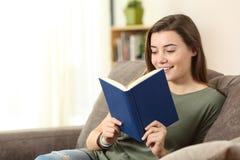 Adolescente che legge un libro su un sofà a casa Fotografia Stock Libera da Diritti