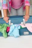 Adolescente che lotta per chiudere valigia piena Fotografie Stock Libere da Diritti