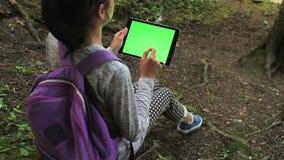 Adolescente che per mezzo del pc della compressa con lo schermo verde archivi video