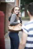 Adolescente che per mezzo del telefono come ritiene intimidita sulla casa della passeggiata immagini stock