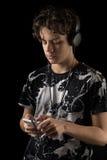 Adolescente che per mezzo del telefono con la cuffia avricolare, isolata sul nero Immagini Stock