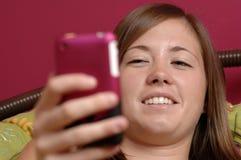 Adolescente che per mezzo del telefono mobile Fotografie Stock